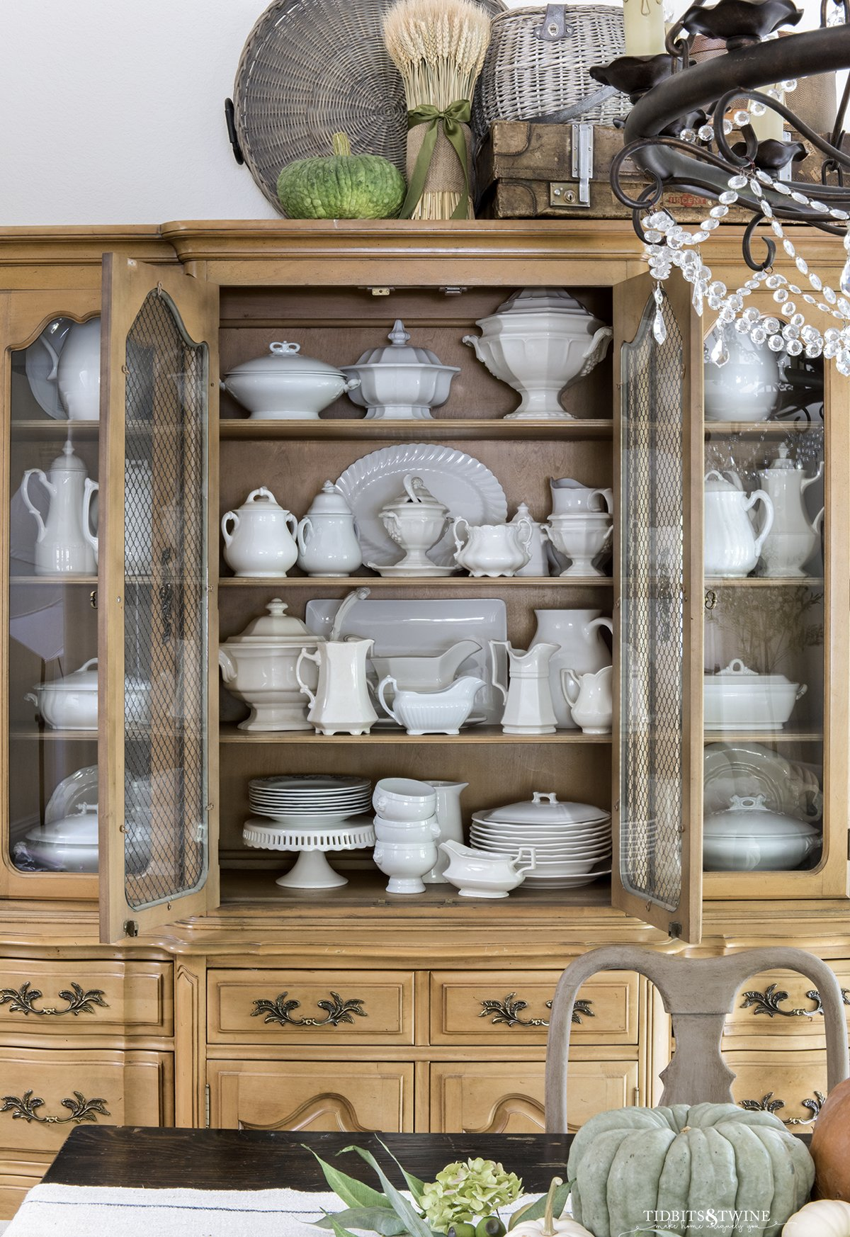 french cabinet full of antique white ironstone collection in a dining room decorated for fall with orange green and white pumpkins