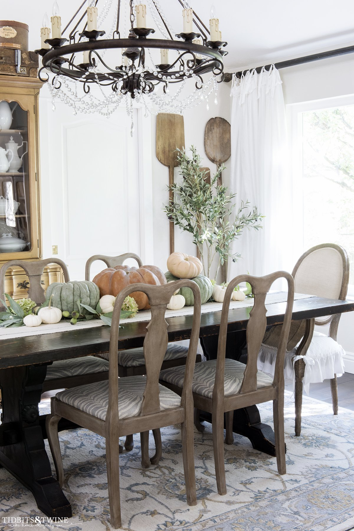 french dining room with gustavian wood chairs and orange green and white pumpkins on the trestle table and antique bread paddles on wall