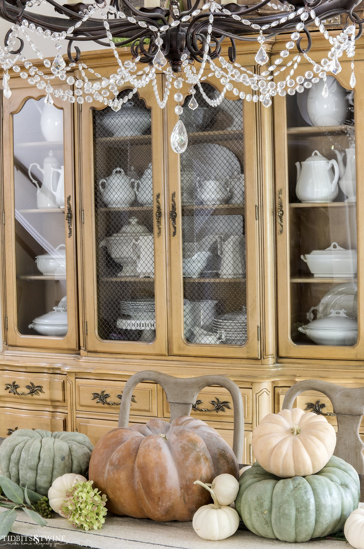 orange green and white pumpkins for fall on dining table with french cabinet against wall full of white ironstone collection