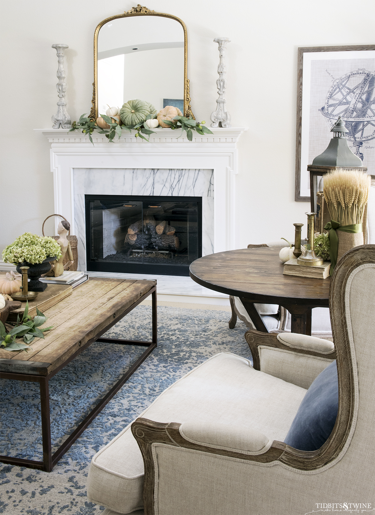 french living room with fireplace decorated for fall and linen wingback chairs