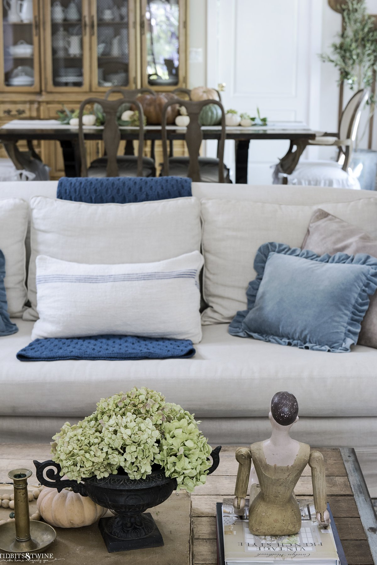 coffee table decorated for fall in front of slipcovered linen sofa with blue throw and dining room in background