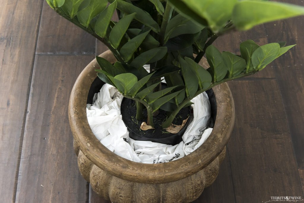 artificial zz plant in brown pot surrounded by stuffed grocery bags