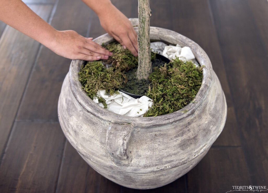 brown clay pot with artificial plant surrounded by stuffed grocery bags and moss being added on top