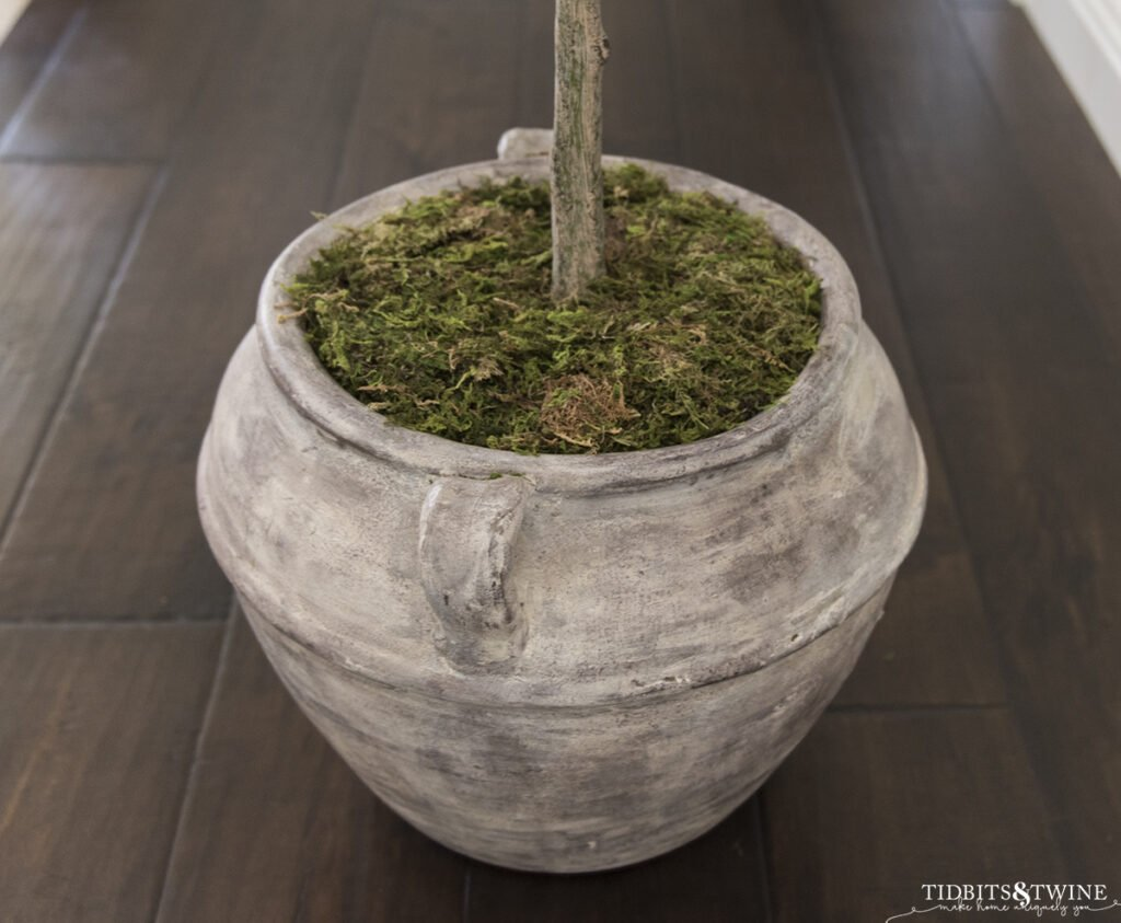 brown clay pot with artificial plant topped with moss to look real