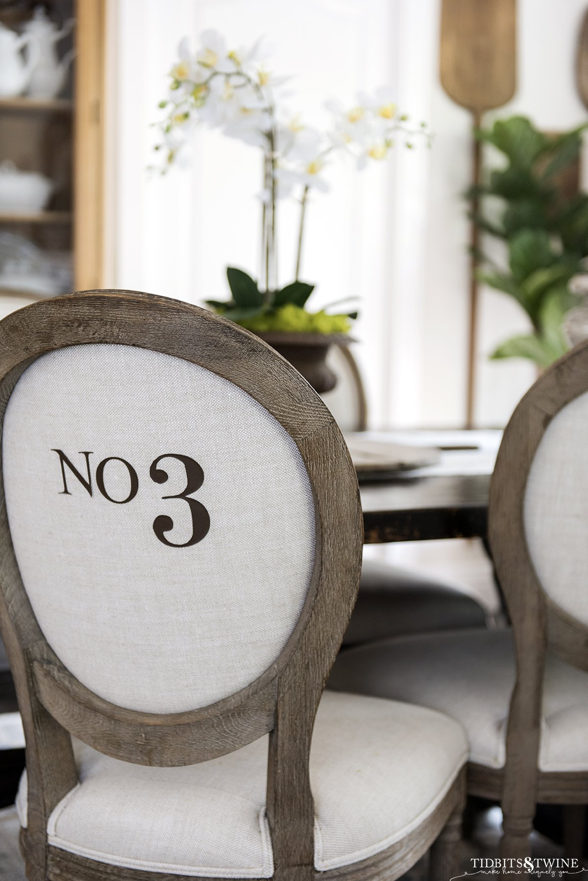 French round back chair with beige linen upholstery with numbers on the back in a dining room with white orchid on table