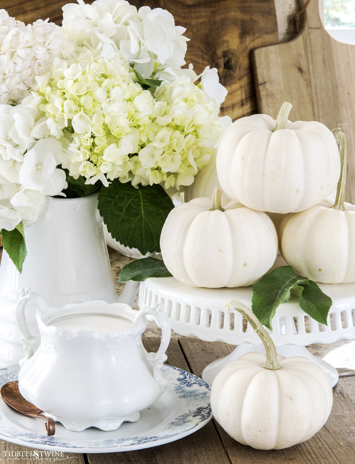 vignette with white pumpkins on a cake stand and white pitcher with white hydrangea and transferware with ironstone sugar bowl