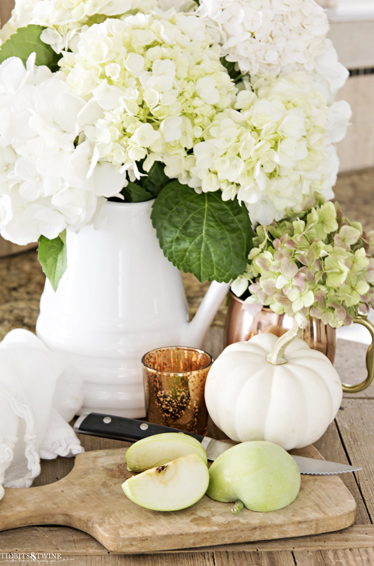 white pitcher with white hydrangeas and copper mug with green hydrangea and cutting board with cut apple