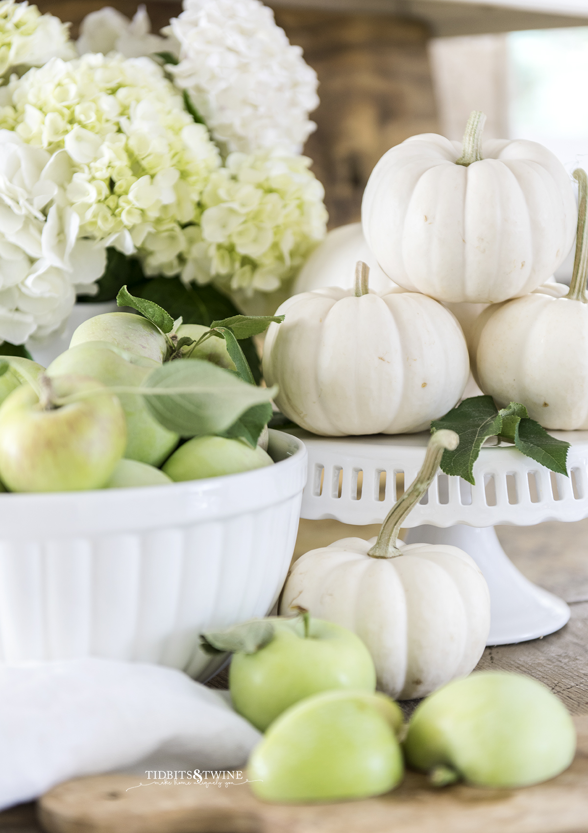 fall kitchen vignette of white bowl full of green apples with white pumpkins on a cake stand and white hydrangea