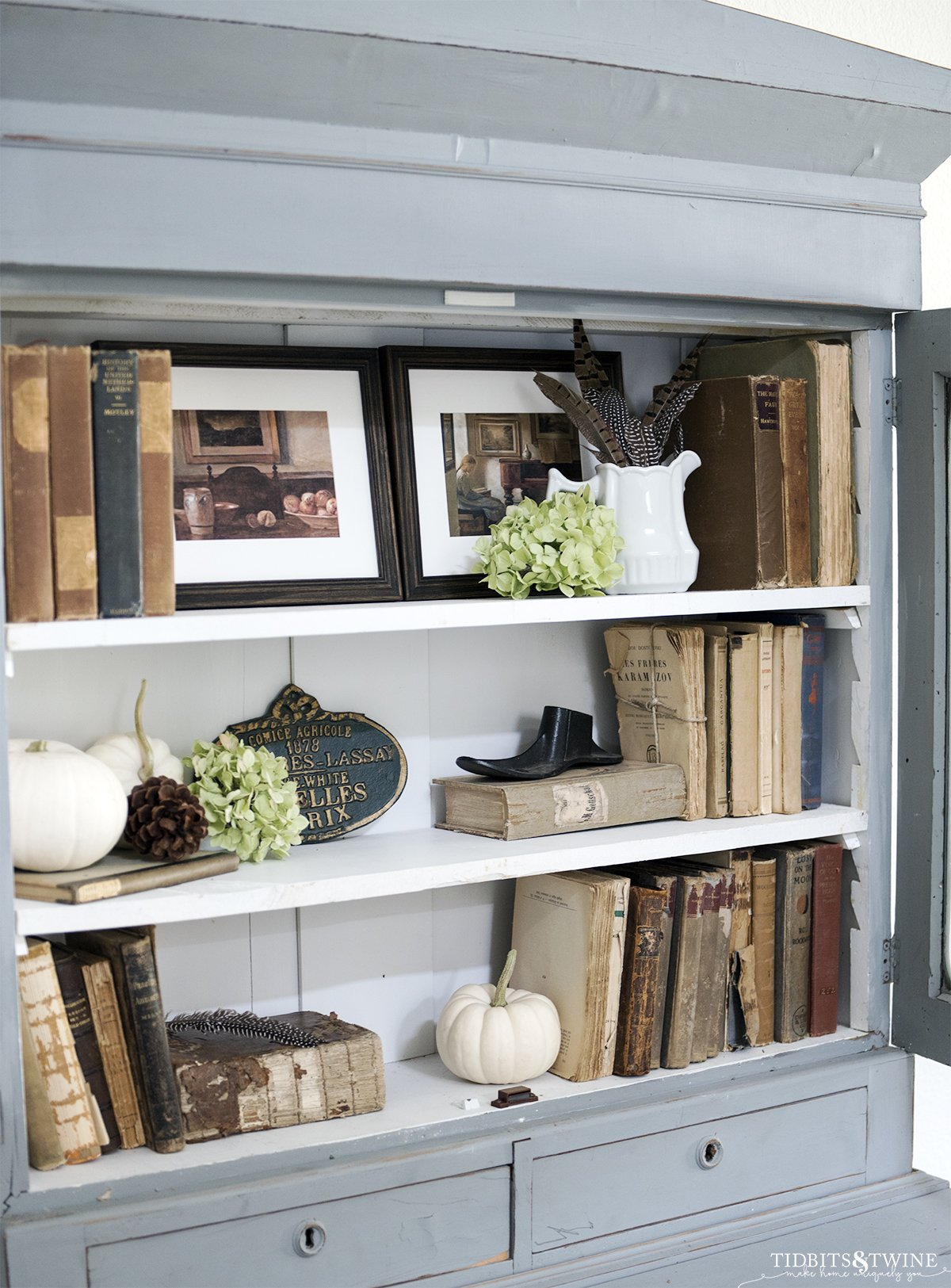 blue cabinet with white shelves decorated with antique books and white pumpkins art and dried hydrangea