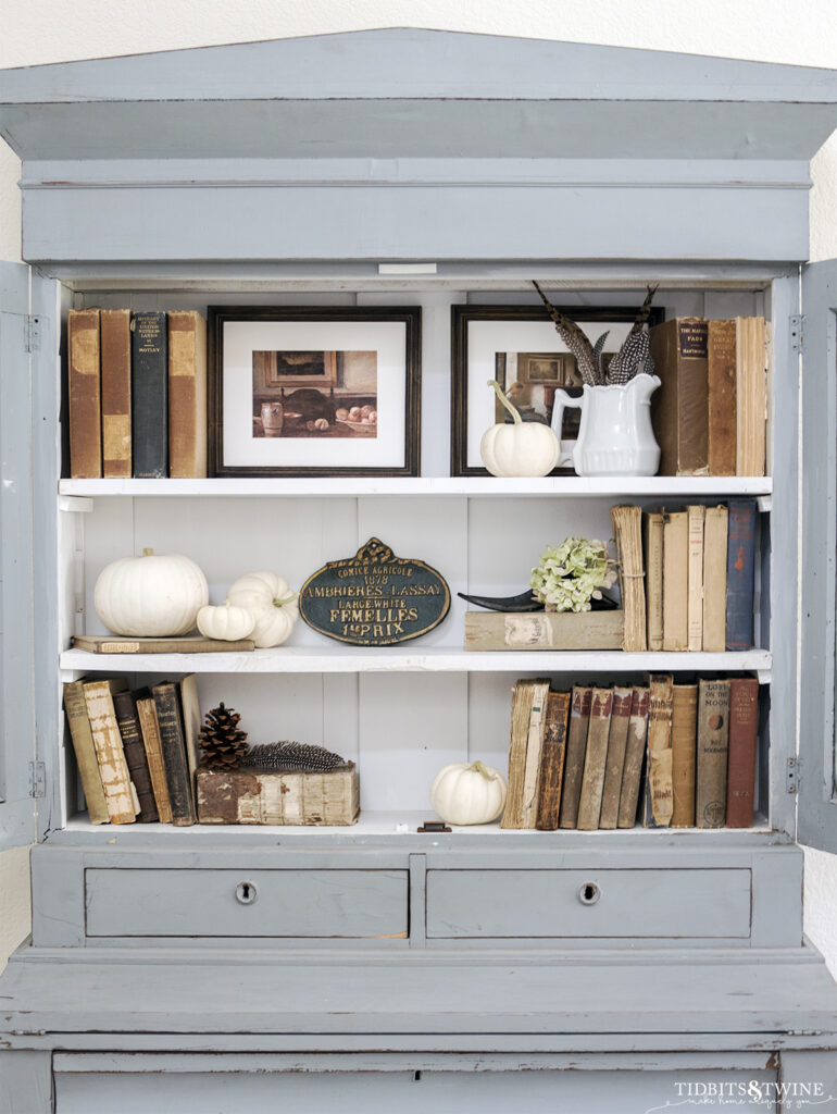 antique blue cabinet with three white shelves styled with old books pumpkins and hydrangea for fall