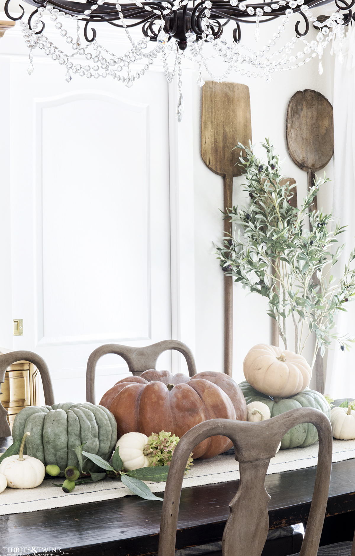 dining room with crystal chandelier and bread paddles on wall orange and green pumpkins down center of table