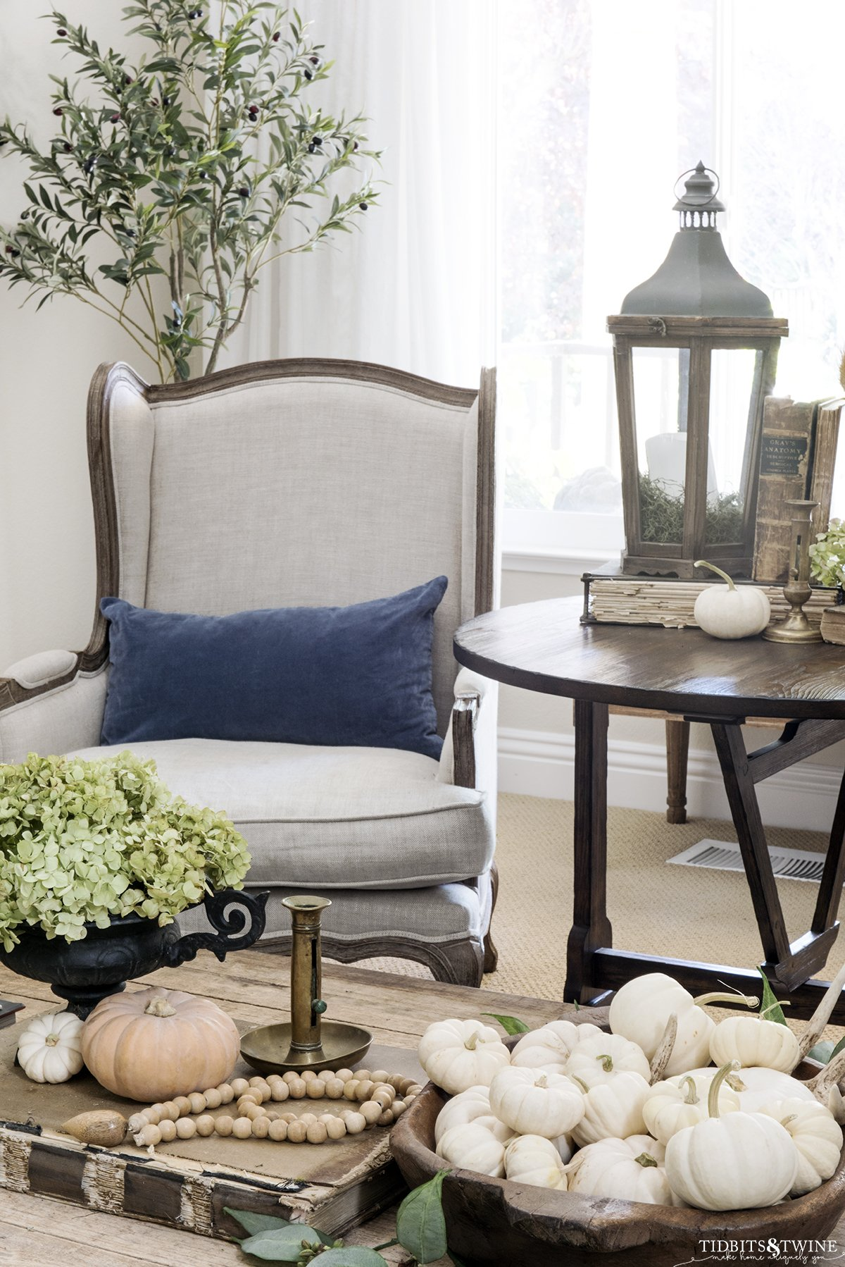 french wingback chair with blue pillow and antique wine tasting table on side and coffee table in front both decorated for fall
